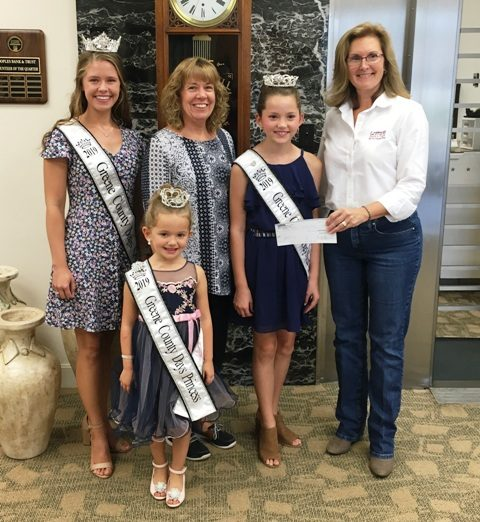 Barbara Price of Peoples Bank and Trust stands with winners of the Greene County Days Pageant.